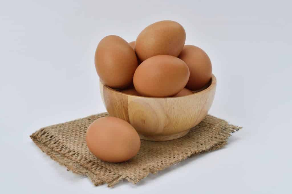 brown-eggs-on-brown-wooden-bowl-on-beige-knit-textile-162712